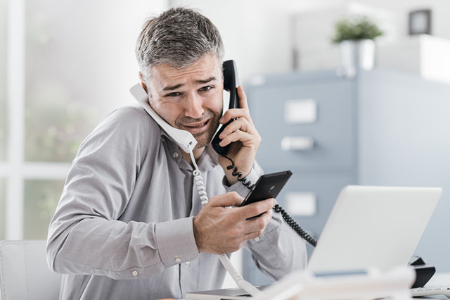 Image of young man on 2 landline handsets and smartphone looking stressed